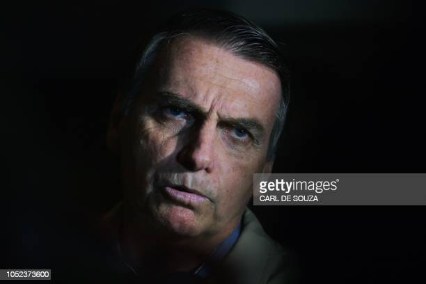 Brazilian farright presidential candidate Jair Bolsonaro speaks to the press during a visit to the Federal Police station in Rio de Janeiro Brazil on...