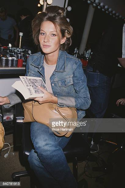 Brazilian fashion model Gisele Bundchen with a copy of the book 'The Lost Books of the Bible and the Forgotten Books of Eden' circa 2000