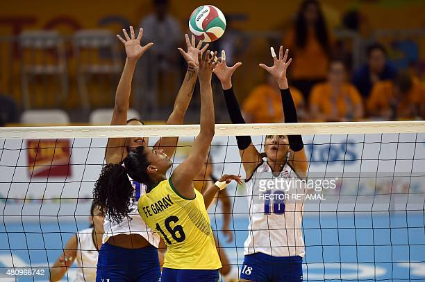 Brazilian Fernanda Rodriguez vies for the ball with Karina Ocasio and Lynda Morales of Puerto Rico during the Volleyball Women Preliminary at the...