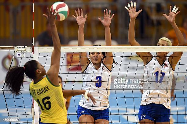 Brazilian Fernanda Rodriguez vies for the ball with Vilmare Mojica and Sheila Ocasio of Puerto Rico during the Volleyball Women Preliminary at the...