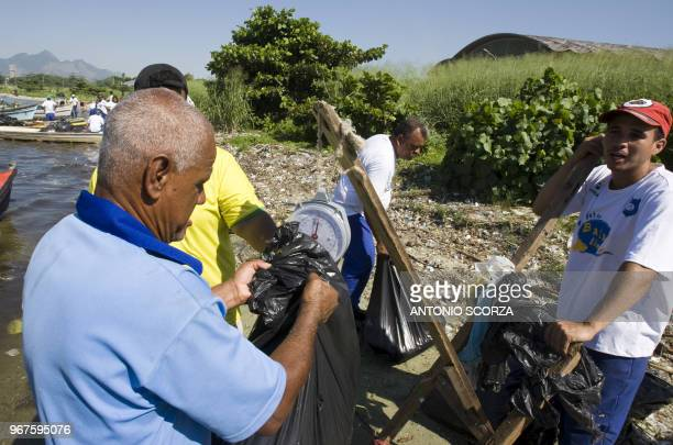 S A Brazilian fisherman weights part of the plastic garbage removed from Catalao Beach inside the Guanabara bay May 6 in Rio de Janeiro Brazil Some...