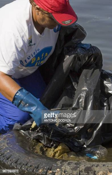 S Brazilian fisherwoman Sandra Morais collects plastic garbage inside a truck tire at Catalao Beach inside the Guanabara bay May 6 in Rio de Janeiro...