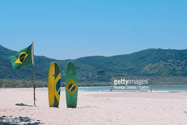 Brazilian Flag By Surfboards At Beach Against Clear Sky