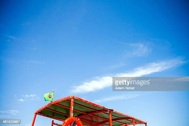 A brazilian flag on top of a boat with blue sky.