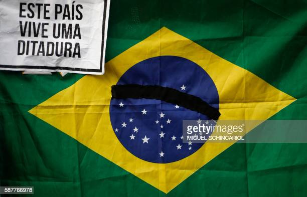 A Brazilian flag with the curved band reading Order and Progress blacked out and a sign proclaiming This country is living in a dictatorship held by...