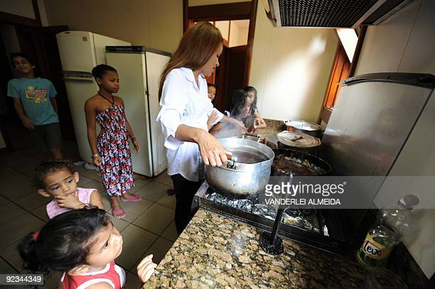 Brazilian Flordelis dos Santos cooks the lunch for her 50 sons four of them her own and another 46 adopted at their home in Niteroi on the other side...