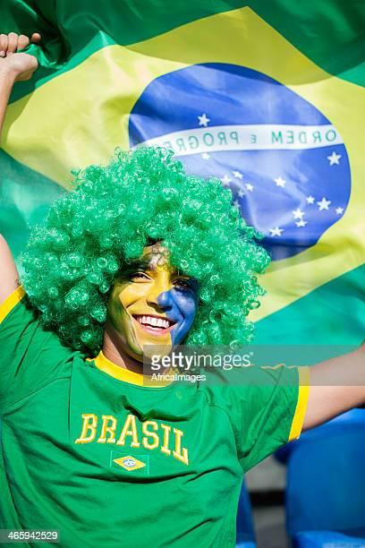 Brazilian football fan waving a flag.