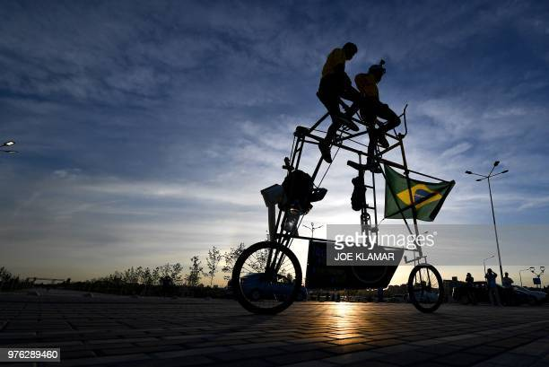 TOPSHOT Brazilian football fans Elias de Souza and his son Elias de Souza junior ride their homemade 3 metrehigh tandem bicycle near Rostov Arena in...