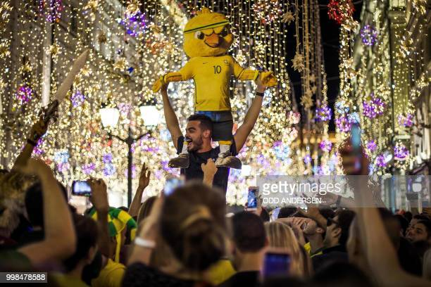 Brazilian football fans hold a yellow chick dummy wearing the number 10 jersey as they party along with tourists and revellers near the Russia 2018...