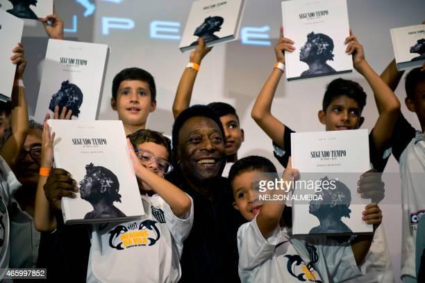 Brazilian football legend Edson Arantes do Nascimento known as 'Pele' poses with children during the autograph ceremony of his book 'Segundo Tempo'...