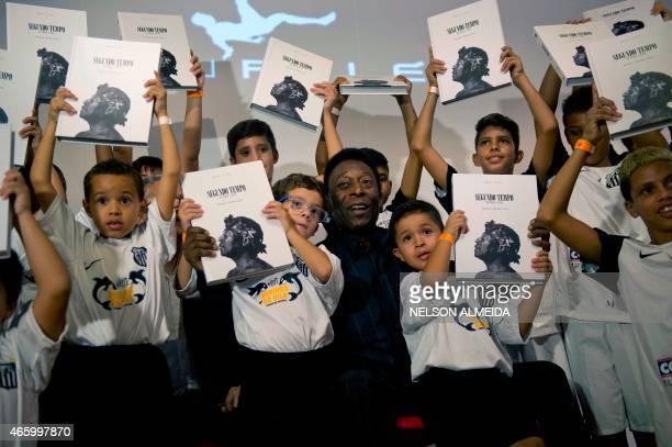 Brazilian football legend Edson Arantes do Nascimento known as Pele poses with children during the autograph ceremony of his book Segundo Tempo in...