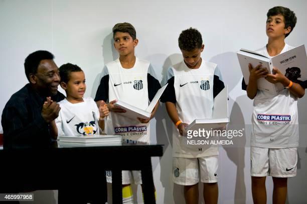 "Brazilian football legend Edson Arantes do Nascimento, known as ""Pele"" , poses with children during the autograph ceremony of his book ""Segundo..."
