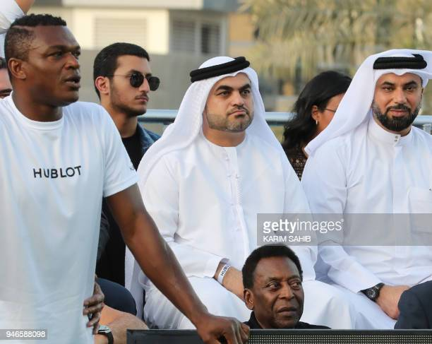 Brazilian football legend Pele and former French defender Marcel Desailly look at a friendly football game at the Dubai Opera gardens in Dubai on...