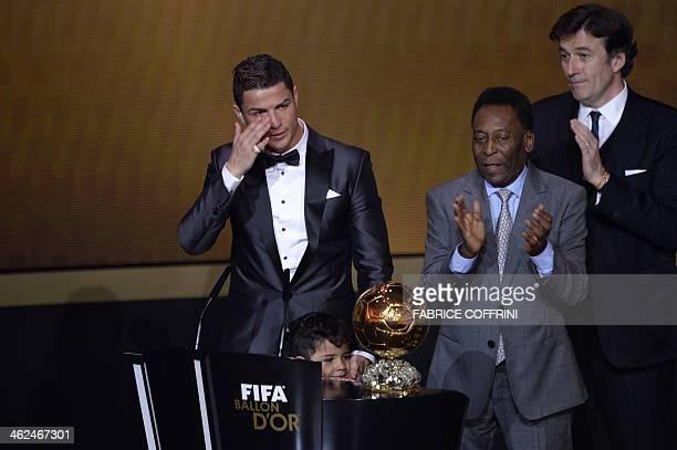 Brazilian football legend Pele applauds next to Real Madrid's Portuguese forward Cristiano Ronaldo as he cries after receiving the 2013 FIFA Ballon...