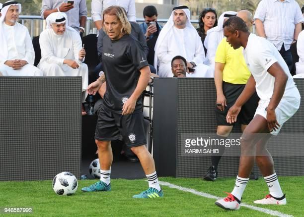 Brazilian football legend Pele looks at former French defender Marcel Desailly and former Spanish defender Michel Salgado at the Dubai Opera gardens...