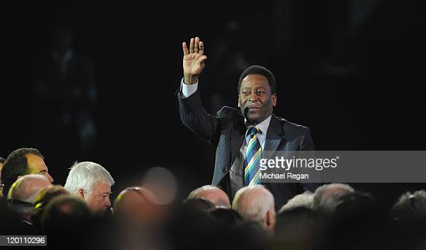 Brazilian football legend Pele waves to the audience during the Preliminary Draw of the 2014 FIFA World Cup at Marina Da Gloria on July 30, 2011 in...