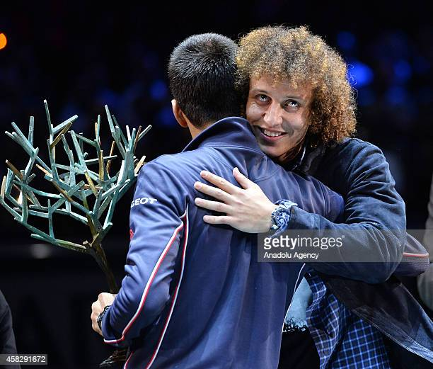 Brazilian football player David Luiz hugs winner Novak Djokovic of Serbia after the Final match of the BNP Paribas Masters held at the at Palais...