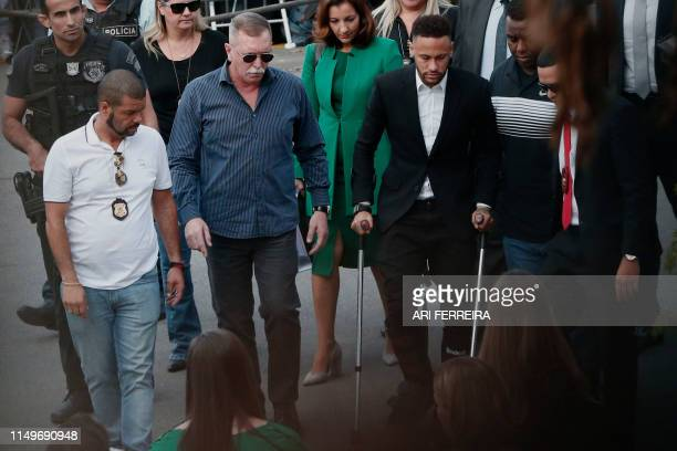 Brazilian football player Neymar arrives on crutches at the Women's Defence Precinct in Sao Paulo Brazil on June 13 2019 to testify after Brazilian...