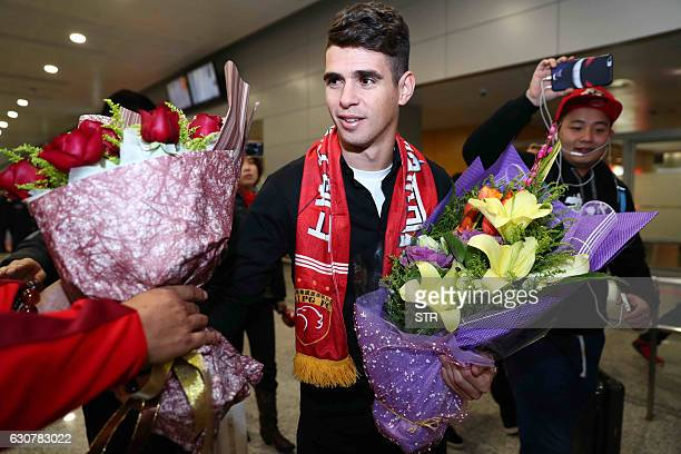Brazilian football player Oscar receives flowers as he arrives at Shanghai airport on January 2 2017 Brazilian midfielder Oscar landed in Shanghai on...