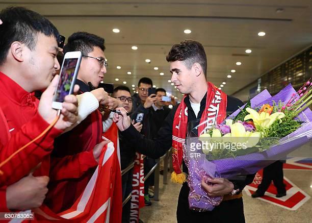 Brazilian football player Oscar signs autographs for Shanghai SIPG fans as he arrives at Shanghai airport on January 2 2017 Brazilian midfielder...