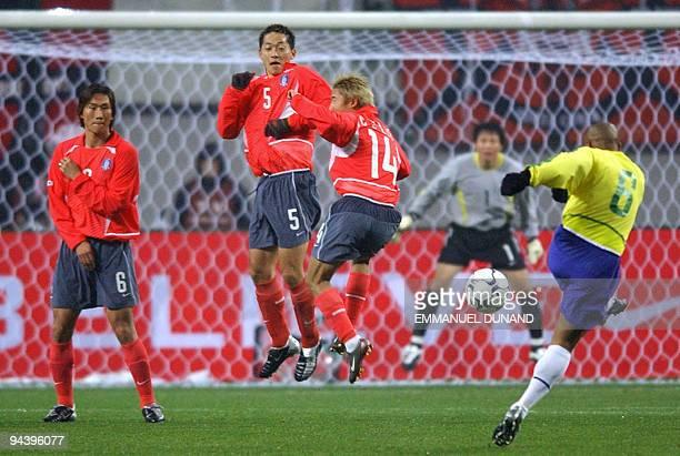 Brazilian football player Roberto Carlos fires a freekick through the South Korean wall of Yoo Sang-Chul, Kim Nam-Il and Lee Chun-Soo 20 November...