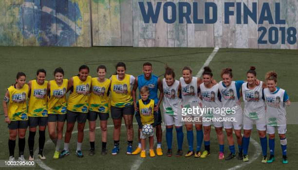 Brazilian football star Neymar poses with his son Davi Lucca and female players before a game during a five-a-side football tournament for his...