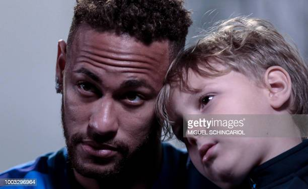 Brazilian football star Neymar, with his son Davi Lucca, offers an interview to AFP on July 21, 2018 at his charity Neymar Junior Project Institute,...