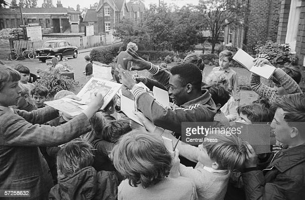 Brazilian football star Pele signing autographs outside the team hotel in Lymm, Cheshire, during the 1966 World Cup in England, July 1966.