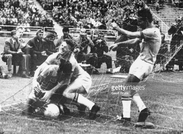 Brazilian football star Pele throws himself over the ball in the net after Brazil scored the single winning goal of the World Cup quarteer final...