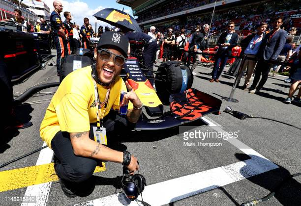 Brazilian football superstar Neymar poses for a photo with the Red Bull Racing RB15 on the grid before the F1 Grand Prix of Spain at Circuit de...