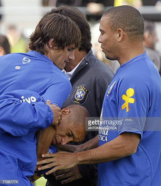 Brazilian footballer Edmilson holds teammate Roberto Carlos by the neck observed by Ronaldo Nazario during a morning training session of Brazil 26...