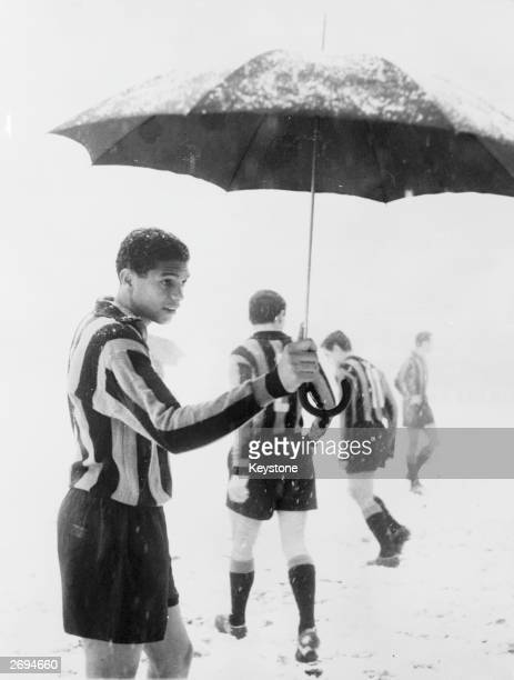 Brazilian footballer Jair holding an umbrella during a snowstorm which caused a game between Inter Milan and Padova to be called off