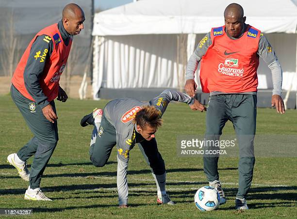 Brazilian footballer Neymar falls between between defenders Luisao and Maicon during a training session on July 5 in Campana 70 Km north from Buenos...