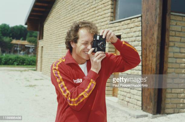 Brazilian footballer Paulo Roberto Falcao, midfielder with AS Roma, pictured taking a photograph with a camera during a training session with the...