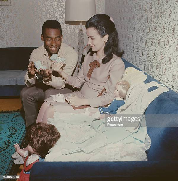 Brazilian footballer Pele and his wife Rosemeri hold baby booties as they prepare for the birth of their child circa 1967