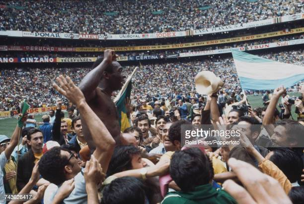 Brazilian footballer Pele is held up on the shoulders of fans and Brazil national football team officials as they celebrate Brazil's 4-1 victory over...