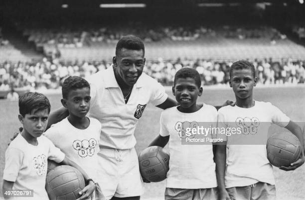 Brazilian footballer Pele lining up in his Santos FC kit with a group of boys wearing Olympic logo tshirts circa 1970