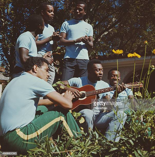 Brazilian footballer Pele plays an acoustic guitar surrounded by Brazil teammates at a training session in Paineiras Brazil before the team leaves...