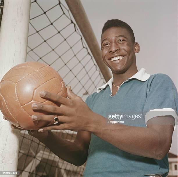 Brazilian footballer Pele posed holding a football next to a goal circa 1965