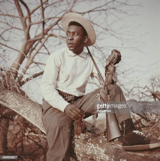 Brazilian footballer Pele posed holding a shotgun and a number of dead birds whilst on a shooting trip circa 1960