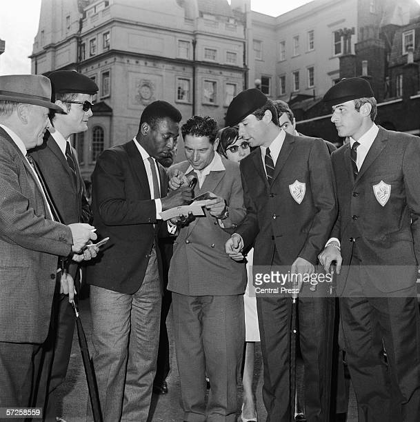 Brazilian footballer Pele signing autographs for members of the French squad at Lancaster House London after attending the reception for teams...