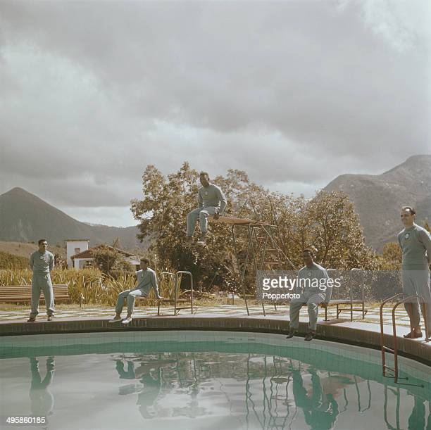 Brazilian footballer Pele sits in centre on a high diving board surrounded by Brazil national football squad teamates posed on the edge of a swimming...