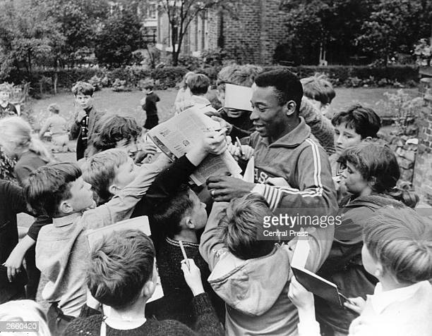 Brazilian footballer Pele surrounded by young autograph hunters