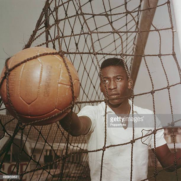 Brazilian footballer Pele wearing a Santos FC shirt retrieves a ball from the goal net circa 1960