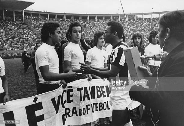 Brazilian footballer Pele wearing his Santos FC kit talking to a group of boys at a match 2nd August 1974