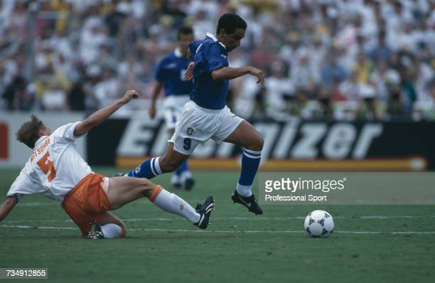 Brazilian footballer Zinho makes a run with the ball as Dutch footballer Rob Witschge slides in for a tackle during play in the 1994 FIFA World Cup...