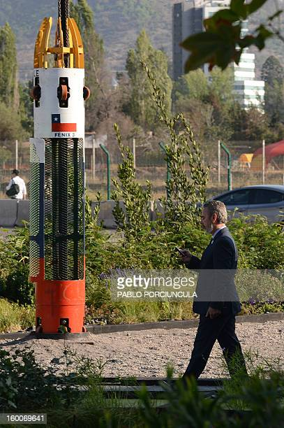 Brazilian Foreign Minister Antonio Patriota checks his mobile phone as he walks near the capsule used to rescue Chilean miners trapped underground...