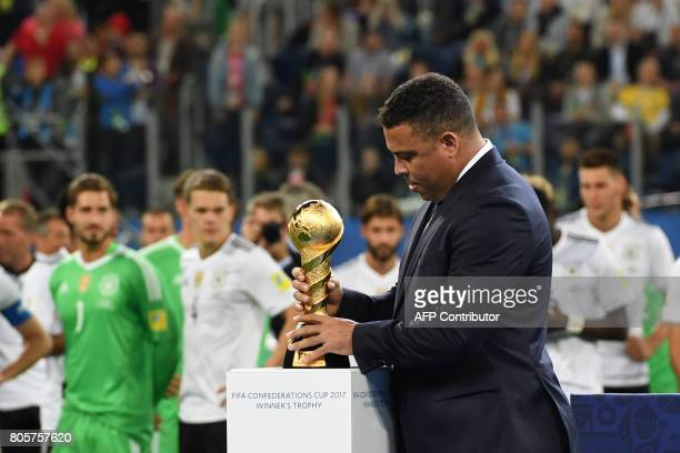 Brazilian former ace footballer Ronaldo holds the winner's trophy during the awards ceremony after Germany beat Chile 10 in the 2017 Confederations...