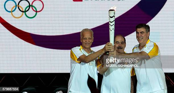 Brazilian former football players Ademir da Guia Rivellino and Zetti pose with the Olympic torch at Anhembi Park in Sao Paulo Brazil on July 24 2016...