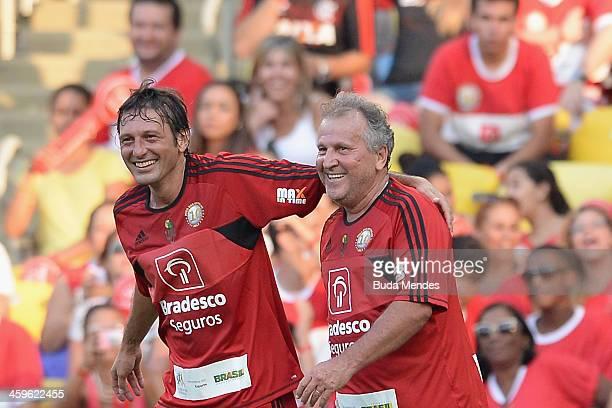 Brazilian former football star Zico celebrates a scored goal with a Leonardo during a charity football match organized by former Brazilian national...